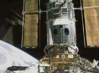 Arrimage de la navette américaine Discovery au télescope spatial Hubble. Crédits : NASA